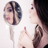 Beautiful woman with lipstick and mirror. Stock Photography