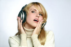 Beautiful woman listening music in headphones Stock Images