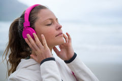 Beautiful woman listening music on headphones at beach Stock Photos