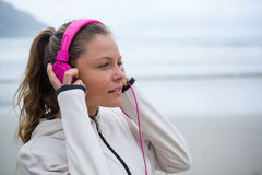 Beautiful woman listening music on headphones at beach Royalty Free Stock Images