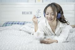 Beautiful woman listening music in headphones on her bed. Woman lying on a cozy bed. Relax concept. royalty free stock photo