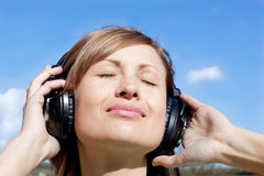Beautiful woman listening music outdoors Royalty Free Stock Images