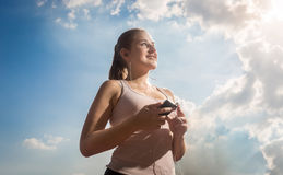 Beautiful woman listening music while running at sunny day Stock Photos