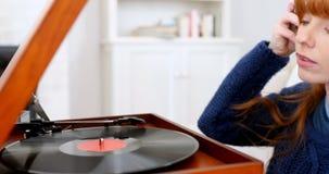 Beautiful woman listening music on turntable 4k. Beautiful woman listening music on turntable in living room 4k stock video footage