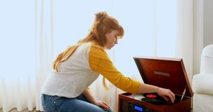 Beautiful woman listening music on turntable 4k. Beautiful woman listening music on turntable in bedroom 4k stock video footage