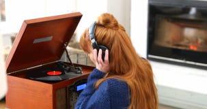 Beautiful woman listening music on turntable 4k. Beautiful woman listening music on turntable in living room 4k stock video
