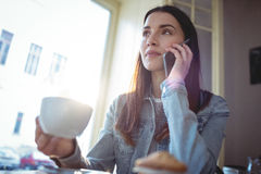 Beautiful woman listening to cellphone at coffee shop Stock Photo