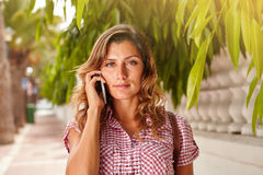 Beautiful woman listening to mobile phone Stock Images