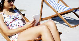Beautiful woman listening to music on digital tablet at beach stock video