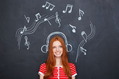 Beautiful woman listening to music in earphones drawn on chalkboard Royalty Free Stock Photo