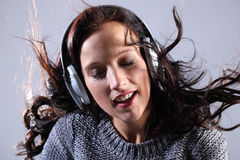 Beautiful woman listening to music on headphones Stock Photos