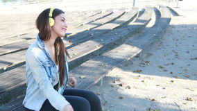 Beautiful woman listening to music on headphones and dancing to the rhythm stock footage