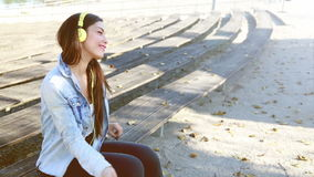 Beautiful woman listening to music on headphones and dancing to the rhythm stock video