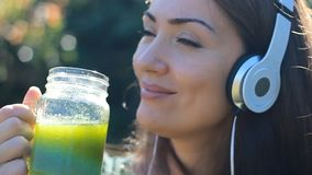 Beautiful woman listening to music with headphones and drinking green smoothies outdoor on a sunny summer day.
