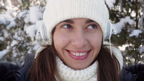 Beautiful woman listening to music. With headphones in the street in winter stock video