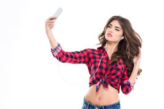 Beautiful woman listening to music and making selfie with smartphone Royalty Free Stock Images
