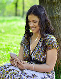 Beautiful woman listening to music outdoors royalty free stock photography