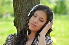Beautiful woman listening to music outdoors Stock Photo