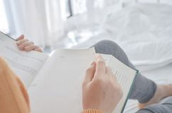 Women are reading a book holding a black glass. stock photos