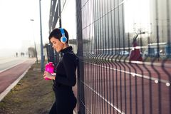 Woman listening to music while working out and jogging outdoor Stock Images
