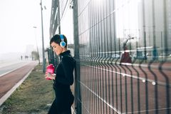 Woman listening to music while working out and jogging outdoor. Beautiful woman listening to music while working out and jogging outdoor Royalty Free Stock Images