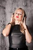 Beautiful woman listening to music. Beautiful young woman listening to music with headphones on grey background royalty free stock image