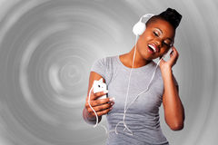 Beautiful woman listening to music. Beautiful young woman with headphones and mobile device listening grooving singing to music, gray circular background Royalty Free Stock Photo