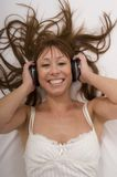 Beautiful woman listens music. In bed with closed eyes using earphones stock photos