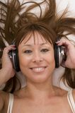Beautiful woman listens music in bed. With closed eyes using earphones royalty free stock images
