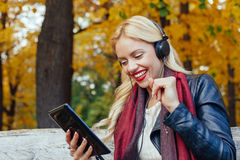 Beautiful woman listens to the music through a digital tablet Royalty Free Stock Image