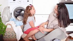 Beautiful woman and little girl assistant near the washing machine and a heap of laundry for washing.