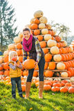 Beautiful woman with little girl holding pumpkins on farm Royalty Free Stock Image