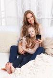 Beautiful woman and little girl putting makeup on Stock Photos