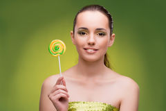 The beautiful woman with lollipop on green background Stock Image