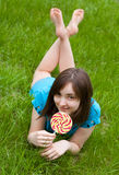 Beautiful woman with lollipop lying on the grass Stock Images