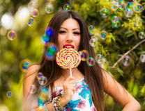 Beautiful woman with lollipop playing with bubbles Stock Images