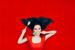 Beautiful Woman With Lollipops on Red Background Royalty Free Stock Images