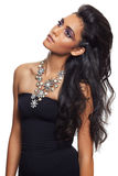 Beautiful woman with long black curly hair. Tanned skin and dramatic make-up wearing black dress and a flower expensive necklace over white background royalty free stock images