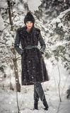 Beautiful woman in long black fur coat and cap enjoying the winter scenery in forest. Brunette girl posing under snow-covered tree Royalty Free Stock Images