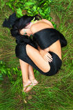 Beautiful woman with long black hair lying on green grass Stock Photo