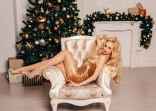 Beautiful woman with long blond hair in elegant dress posing near decorated Christmas tree. Fashion interior photo of beautiful woman with long blond hair in stock photography