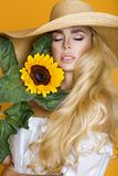 Beautiful woman with long blond hair, wearing a white dress and hat, holding sunflowers. Beautiful woman model girl with long blond hair, wearing a white dress Royalty Free Stock Photography