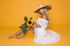 Beautiful woman with long blond hair, wearing a white dress and hat, holding sunflowers. Beautiful woman model girl with long blond hair, wearing a white dress Royalty Free Stock Image