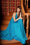 Beautiful woman in a long blue dress in the rich interior. Young Royalty Free Stock Images