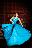 Beautiful woman in a long blue dress in the rich interior. Young Royalty Free Stock Photography