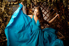 Beautiful woman in long blue dress. Young girl in luxury fashion Royalty Free Stock Photos