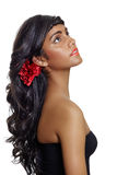 Beautiful woman with long brown curly hair. Portrait of a beautiful tanned young woman with long brown curly hair and red flower, wearing red lipstick and black Royalty Free Stock Photos