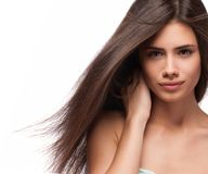 Beautiful woman with long brown hair. Closeup portrait of a fashion model posing at studio. Stock Photos
