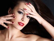 Beautiful woman with long brown straight hairs. And red nails lying on the dark background Stock Photo