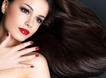 Beautiful woman with long brown straight hairs. And red nails lying on the dark background Stock Images